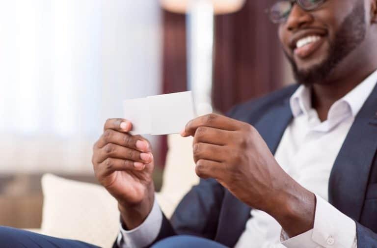 Man in pak met bril op zit op een bank en bekijkt een visitekaartje