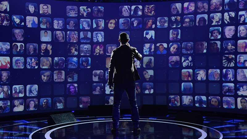 Man staat voor blauw scherm met vele foto's