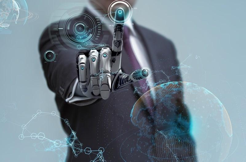 Een man in pak met een robothand bedient een digitaal scherm met lichtgevende pictogrammen