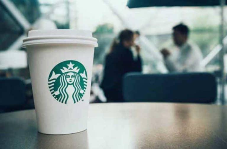 Een Starbucks koffiebeker staat op een houten tafel met op de achtergrond twee mensen die met elkaar praten
