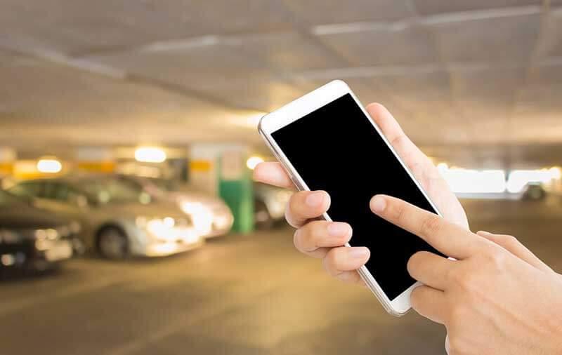 Handen houden smartphone vast in parkeergarage