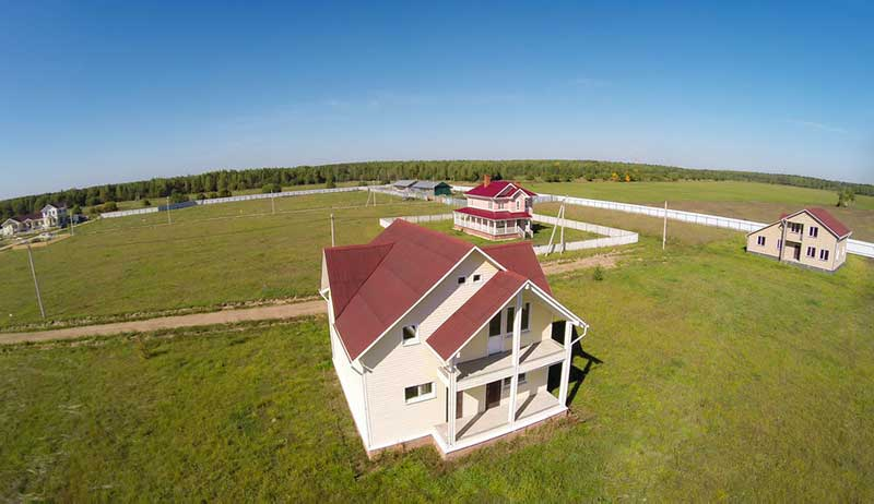 Witte huizen met rode daken in weiland