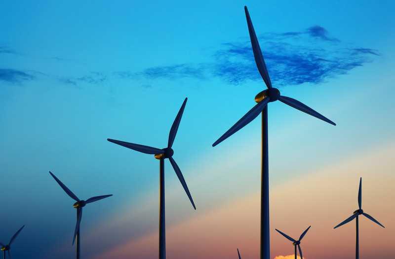 Windmolens tegen gekleurde lucht bij zonsondergang