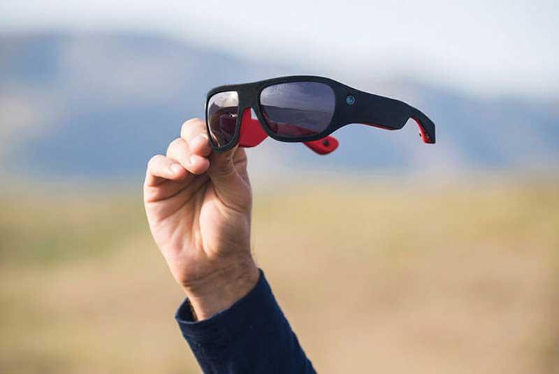 Een hand met zonnebril en veld op de achtergrond