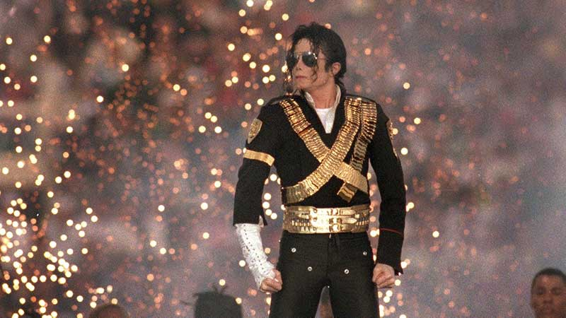 Michael Jackson op een podium met zonnebril en vonkenregen op de achtergrond