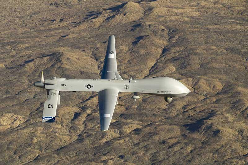 Een militaire drone vliegt boven een dor heuvellandschap