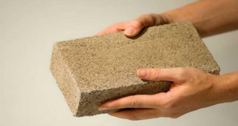 Twee handen houden een BioMASON baksteen vast
