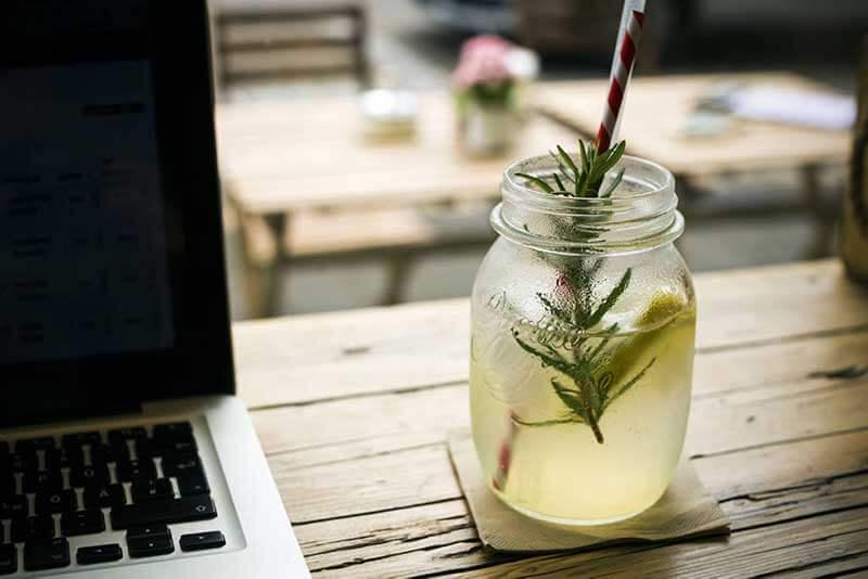 Een glas met frisdrank en een rietje op een houten tafel waarop een laptop staat