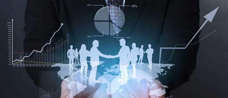 Handen met een holografische afbeelding van silhouetten van mensen die elkaar de hand schudden en op een wereldkaart staan