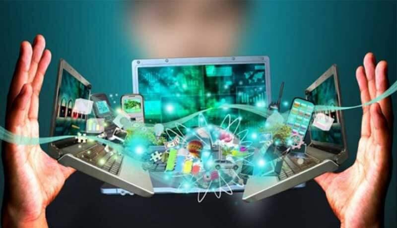 Drie laptops en andere slimme tech zweven tussen twee handen in de lucht