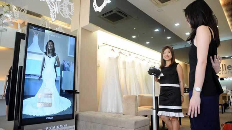 Een vrouw past een virtuele bruidsjurk voor een slimme spiegel, terwijl een andere vrouw naast haar staat