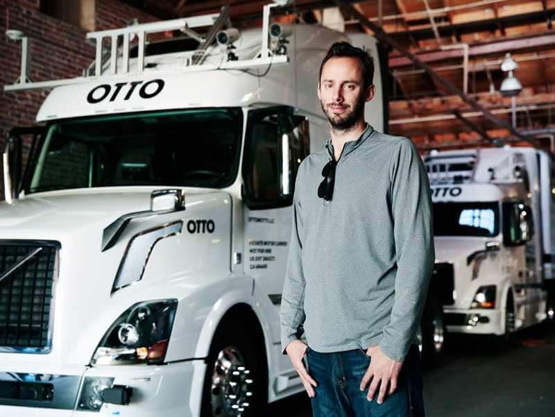 Een man staat voor twee zelfrijdende Otto-vrachtwagens