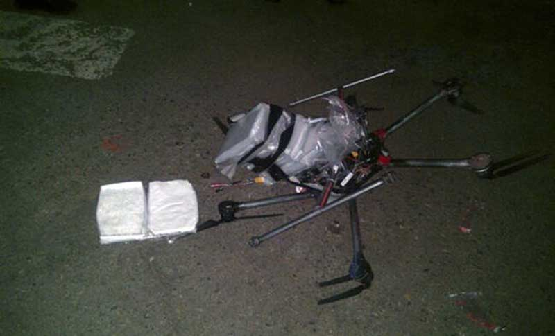 Neergestorte zwarte drone met daarnaast twee pakketjes met wit poeder