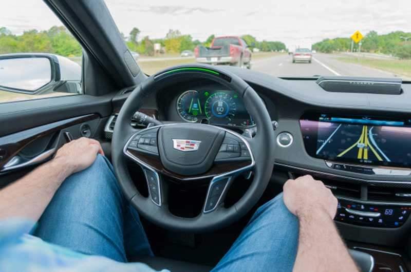 Een man met beide handen op zijn knieën zit in een zelfrijdende auto