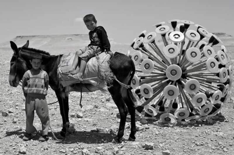 Een jongen zit op een ezel met een andere jongen ernaast met de Mine Kafon-bal op de achtergrond