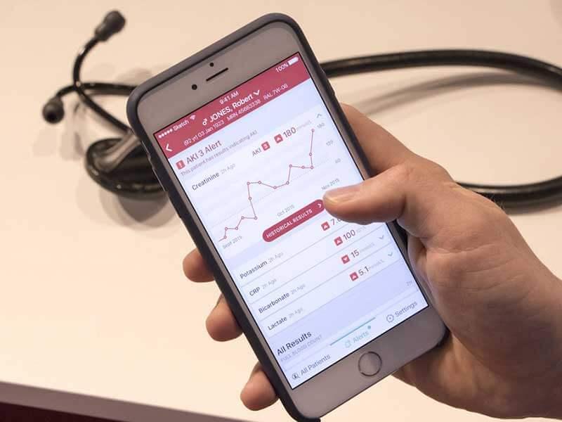 Een hand houdt een smartphone vast met een app met medische dossiers van de patiënt Robert Jones