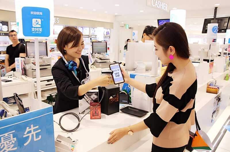 Een meisje in een winkel laat haar smartphone met de Alipay betaalapp door een lachende kassière scannen