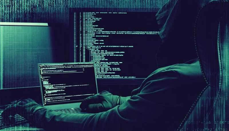 Een man met een hoodie en handschoenen zit voor twee computerschermen en een laptop