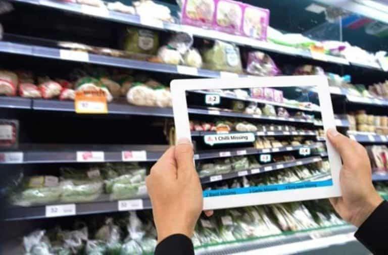 Twee handen houden een tablet vast waarop supermarktartikelen afgebeeld staan||||