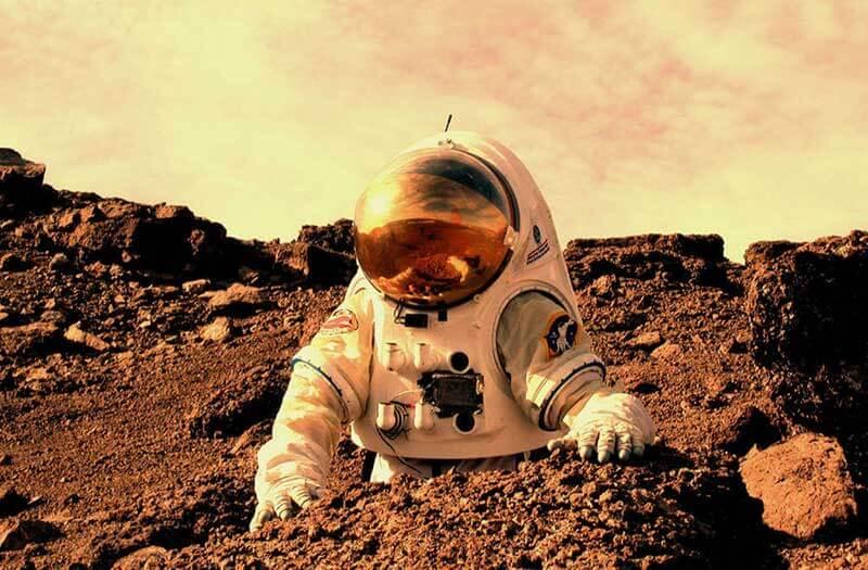 Een man in een wit ruimtepak ingegraven in de grond op Mars