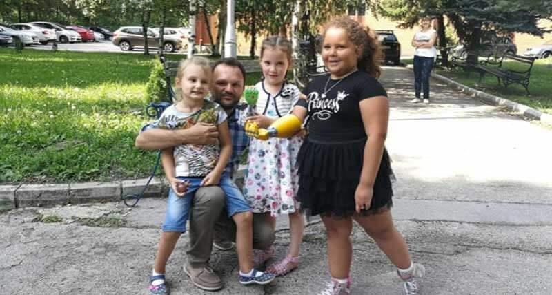 Een man met drie kinderen op straat