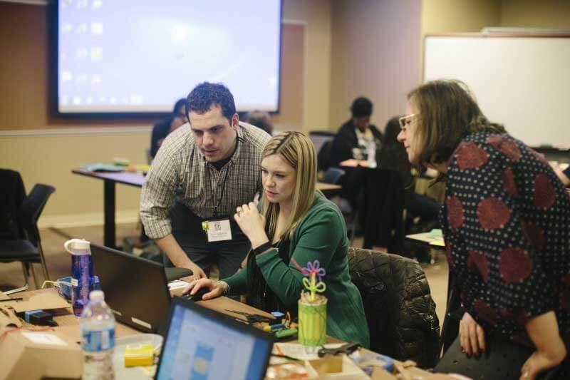 Man and twee vrouwen aan bureau in klaslokaal