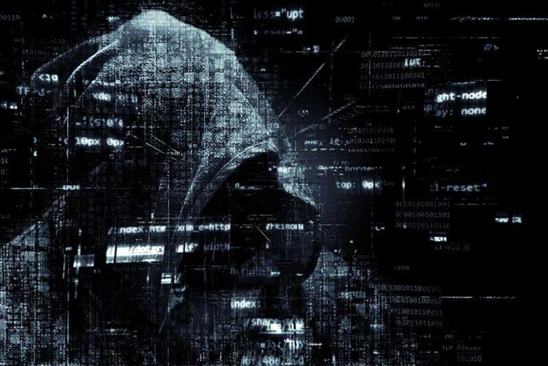 Cybercrimineel met capuchon in donkere kamer