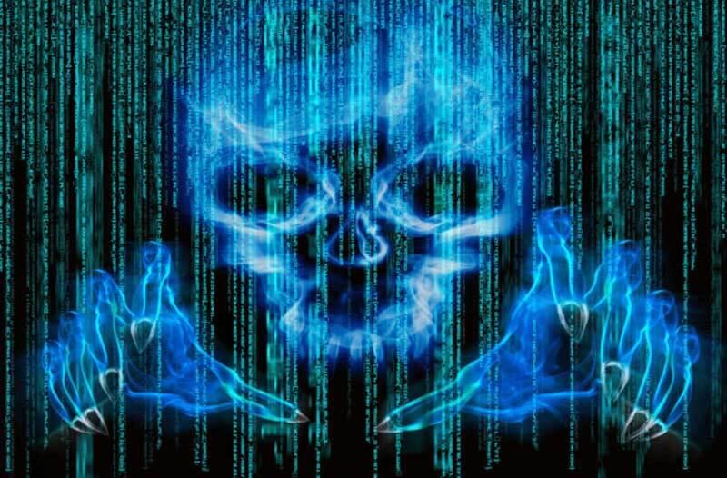 Een digitale afbeelding van een doodshoofd en twee handen op een computerscherm met binaire code