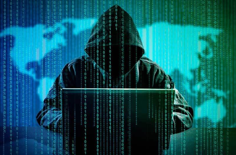 Een hacker met een hoodie zit voor een laptop met op de achtergrond een groen-blauw scherm met de wereldkaart