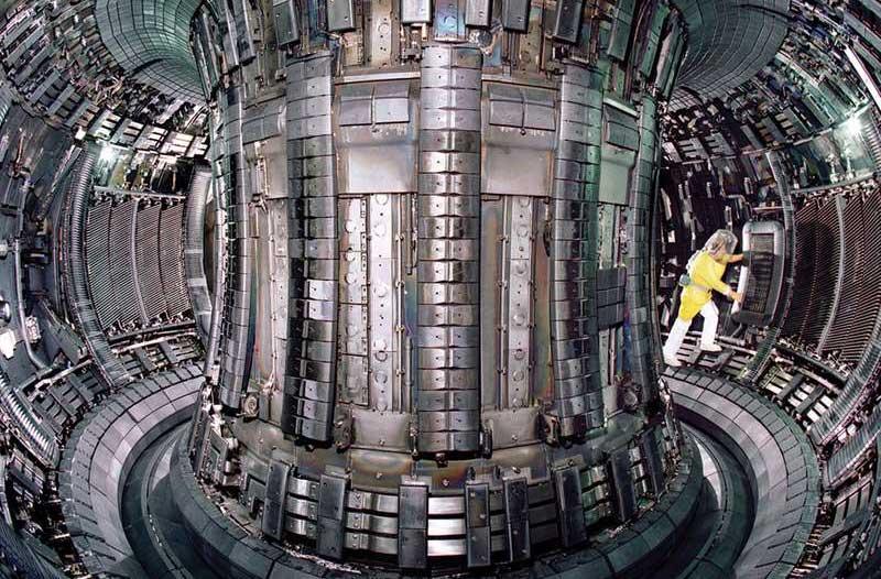 Persoon in geel pak in een kernreactor