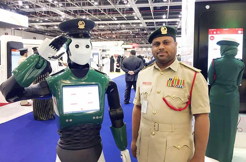 Een politierobot staat naast een menselijke politieagent