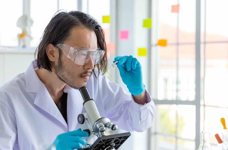 Man in witte laboratoriumjas en speciale bril kijkt naar iets onder de microscoop