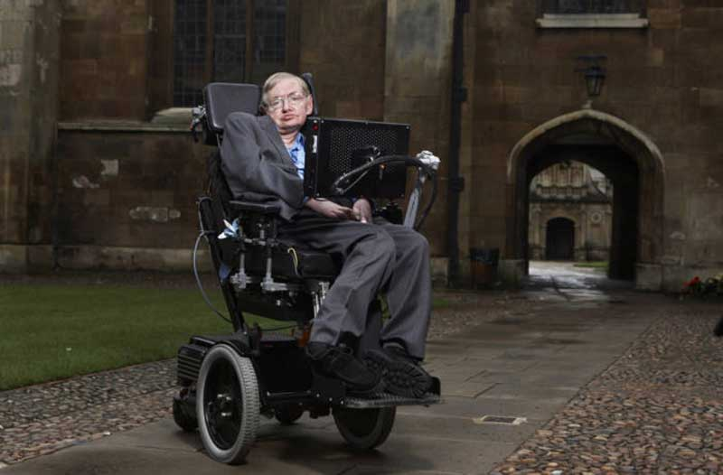 Physicist Stephen Hawking sitting in his wheelchair in front of an old building