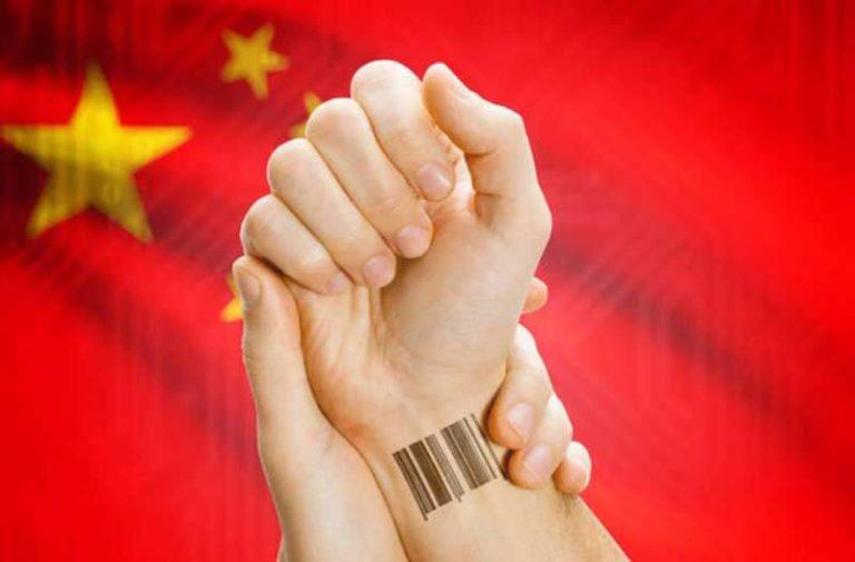 Een hand met een streepjescode op de pols wordt door een andere hand vastgehouden met de Chinese vlag op de achtergrond