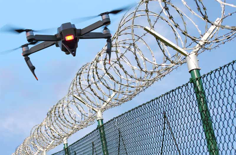 Drone flying over a barbed-wire fence