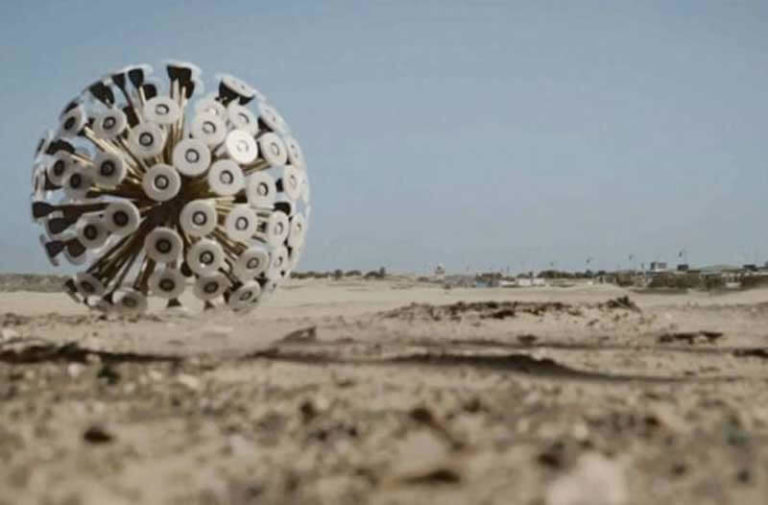 Een grote, futuristisch uitziende rollende bal in een woestijnlandschap