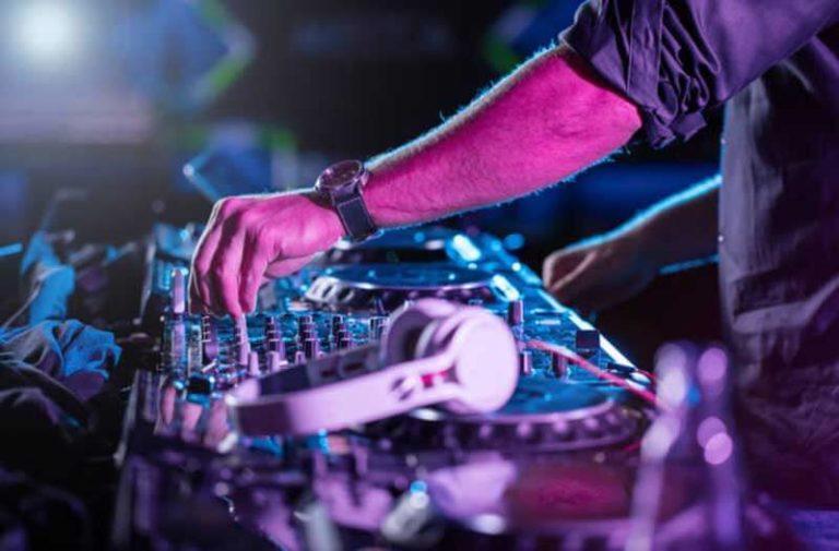 De arm van een DJ die aan de knoppen van een mixpaneel draait waarop een koptelefoon ligt