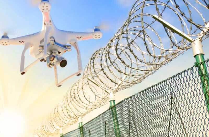 Witte drone met een camera die boven een prikkeldraadomheining zweeft