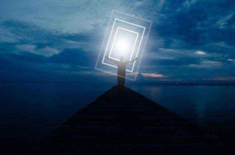 Man staat op een heuvel aan de waterkant in de avond en houdt een groot verlicht rechthoekig scherm omhoog|Man standing on hill on edge of water at night holding illuminated rectangular screen up high