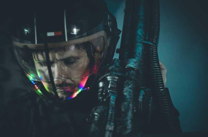 Man met een wapen en een futuristische helm die een lichtgevende vloeistof bevat