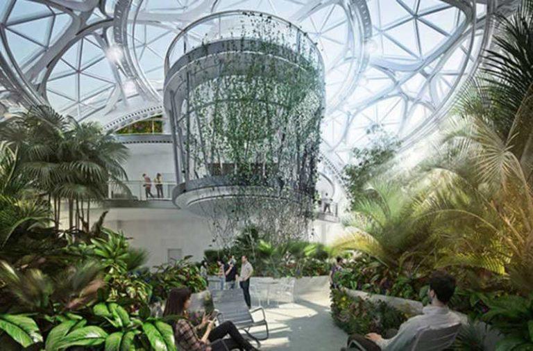 Glazen gebouw vol met planten en veel natuurlijk licht waar mensen werken