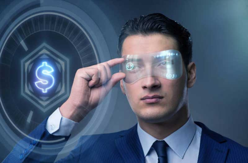 A man in a suit wearing futuristic glasses interacts with a holographic display