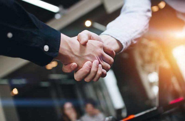 Twee mannen schudden elkaar de hand op kantoor