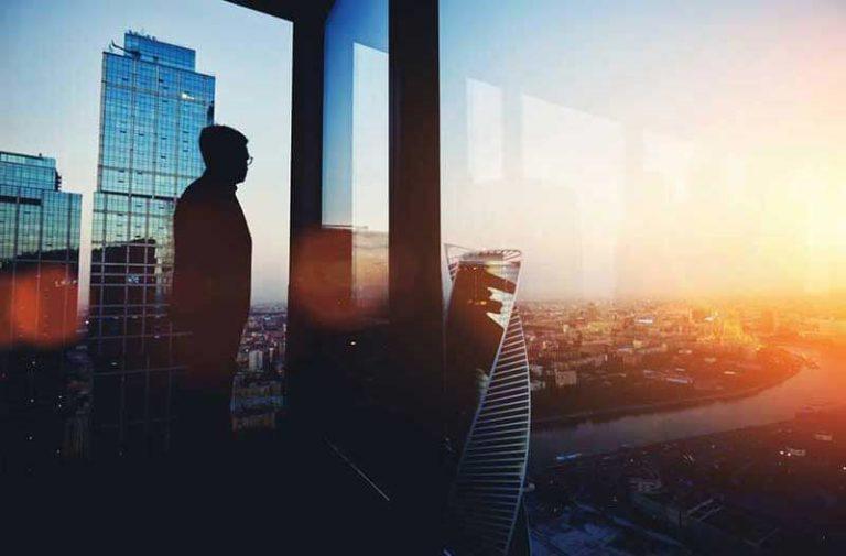 Man in wolkenkrabber kijkt naar zonsondergang over stad