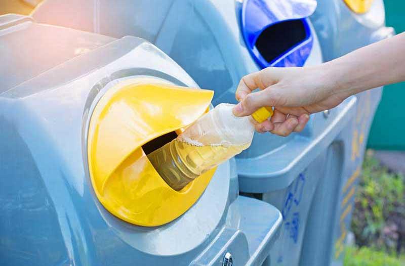 Close-up van de rechterhand van een persoon die een halfvol plastic flesje in een gele afvalbak doet