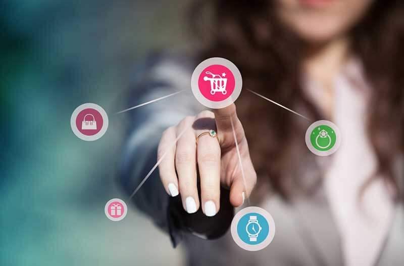 Een wazige foto van een vrouw die wijst naar een digitale pictogram van een winkelwagentje en andere pictogrammen