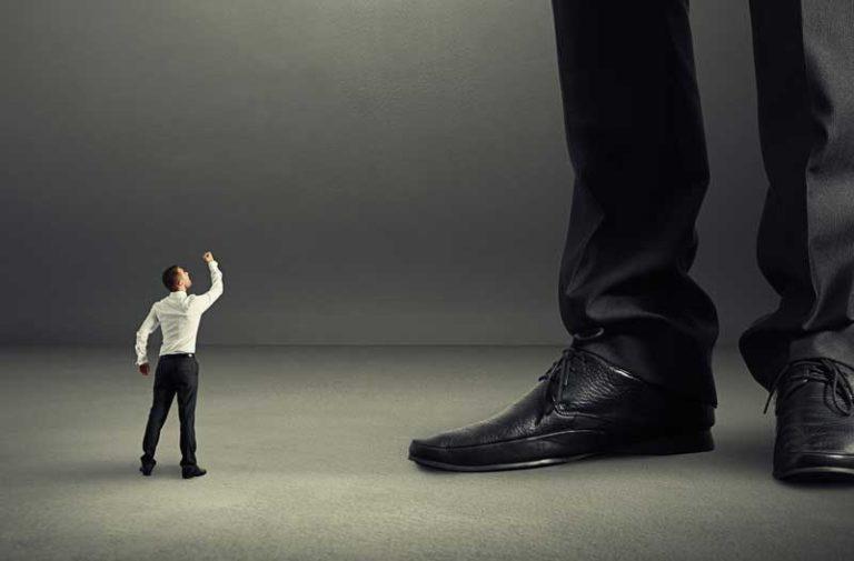 Een klein mannetje zwaait dreigend met zijn hand naar een grote persoon waarvan alleen de broek en zwarte schoenen zichtbaar zijn