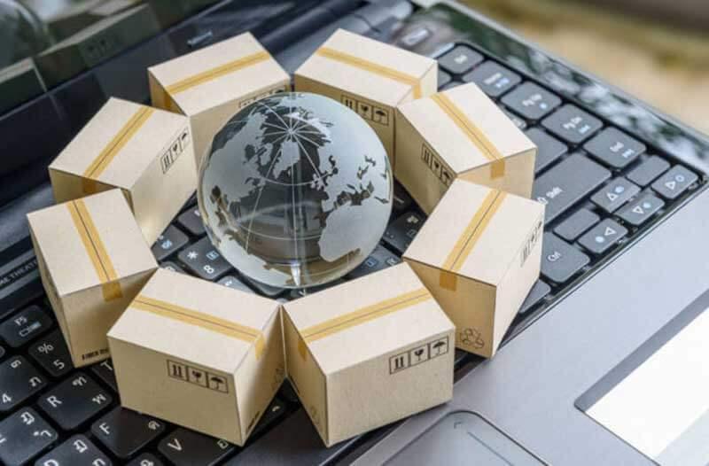 Een kleine glazen wereldbol op een keyboard omgeven door kartonnen doosjes