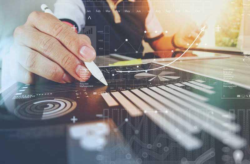 Close-up van een rechterhand met een potlood boven een staafdiagram op een bureau