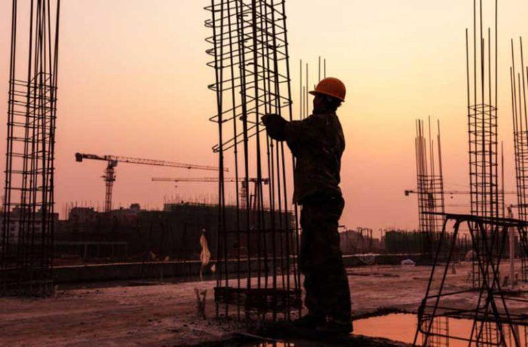 Bouwvakker werkt aan stalen constructie tijdens zonsondergang
